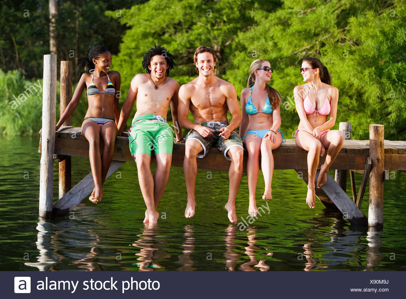Five young friends in swimwear sitting side by side on lake jetty front view smiling portrait Stock Photo