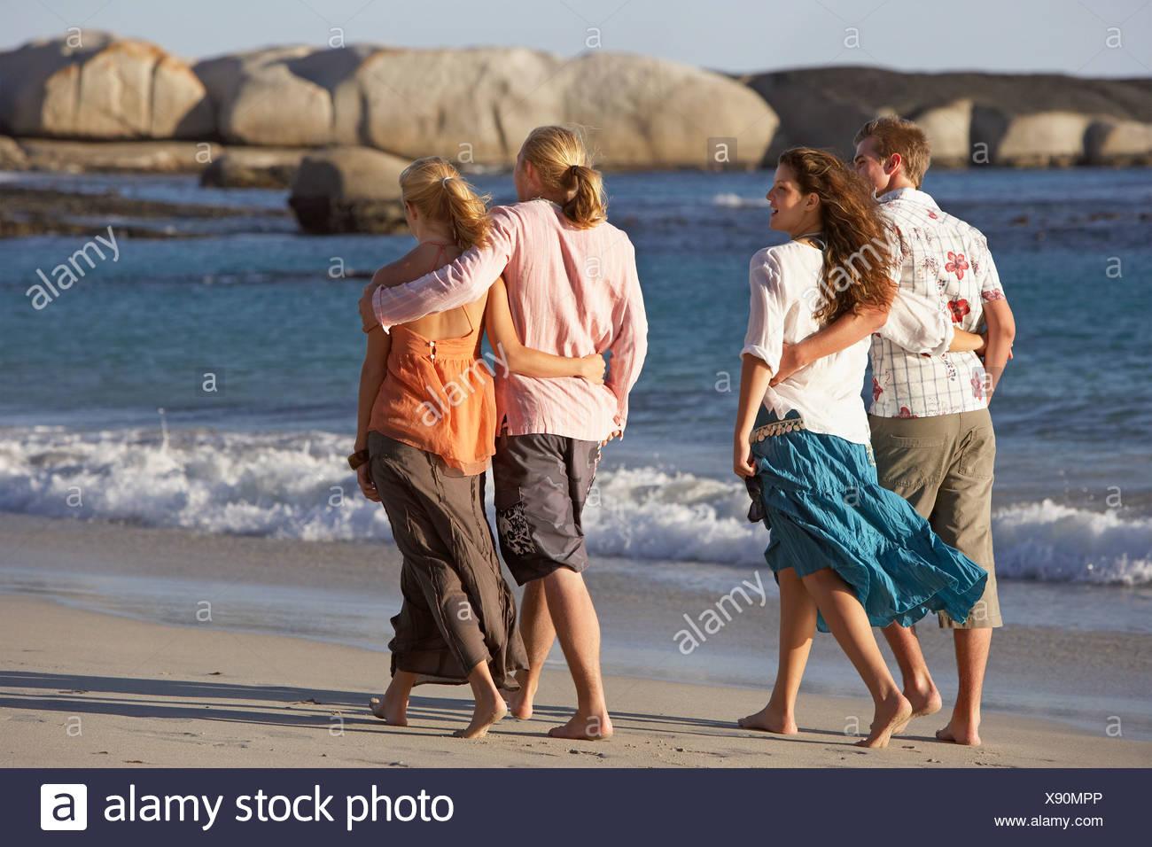 Two teenage couples 17 19 walking on beach near water s edge arm around waist rear view - Stock Image