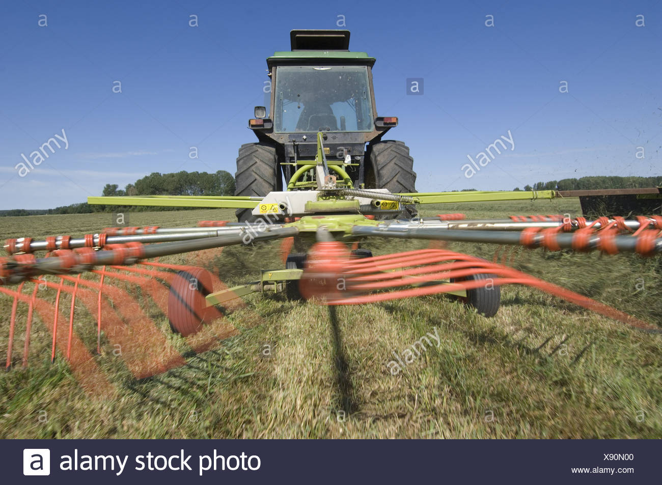 Tractor with Claas Liner 350 rotary rake, turning cut grass