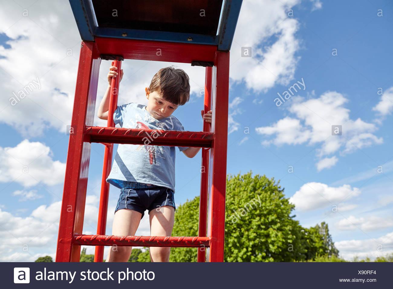 Boy climbing metal ladder - Stock Image