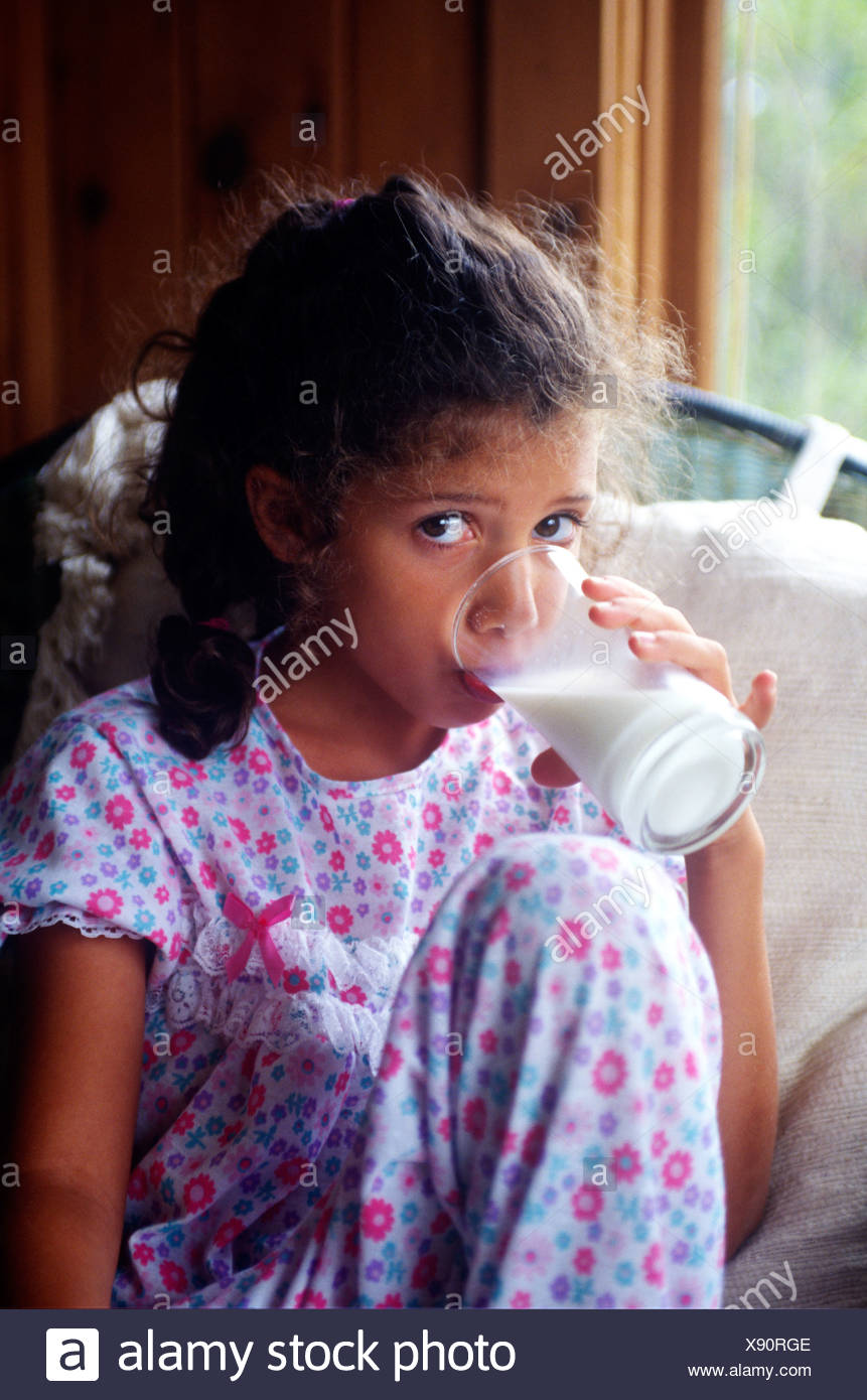 Young girl drinking a glass of milk in her pajamas - Stock Image