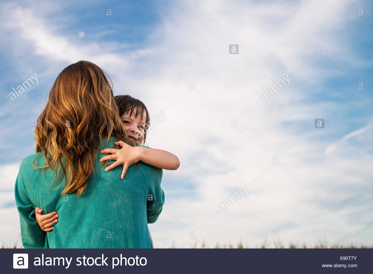 Mother carrying her daughter on her shoulder - Stock Image