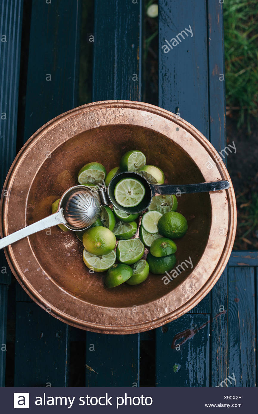 Fresh green lime in a bowl, squeezed for cocktails - Stock Image