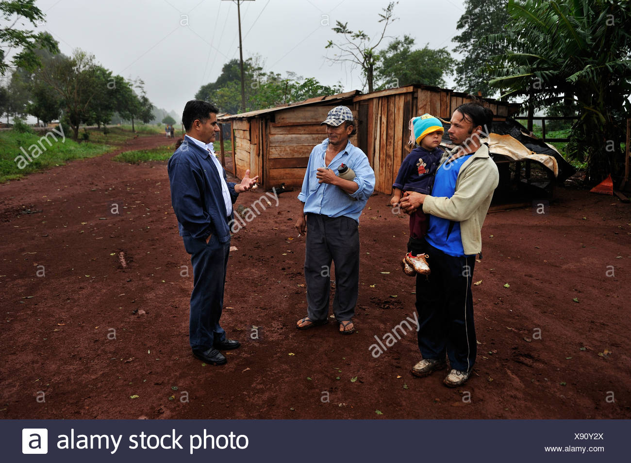 Human rights activists talking to smallholders who live in makeshift huts by the roadside, the farmers were forced off their - Stock Image