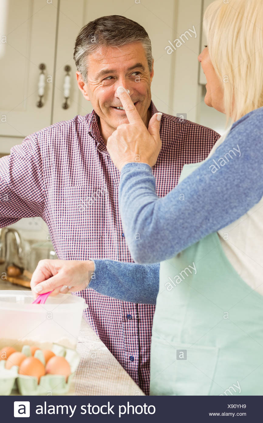 Happy woman putting flour on husbands nose - Stock Image