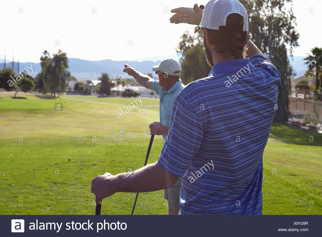 Two male golfers looking and pointing direction - Stock Image