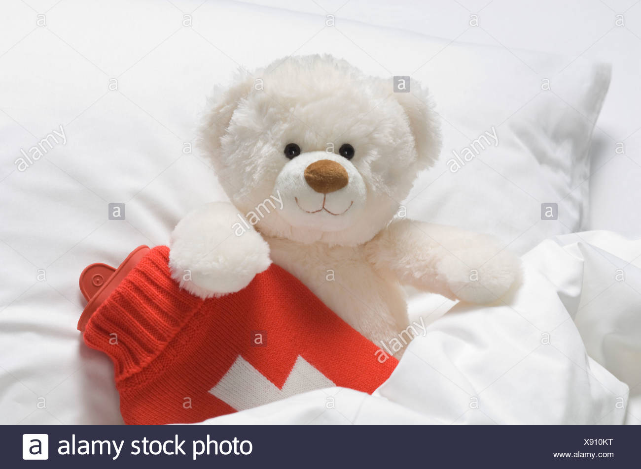 Teddy bear with hot water bottle on bed - Stock Image