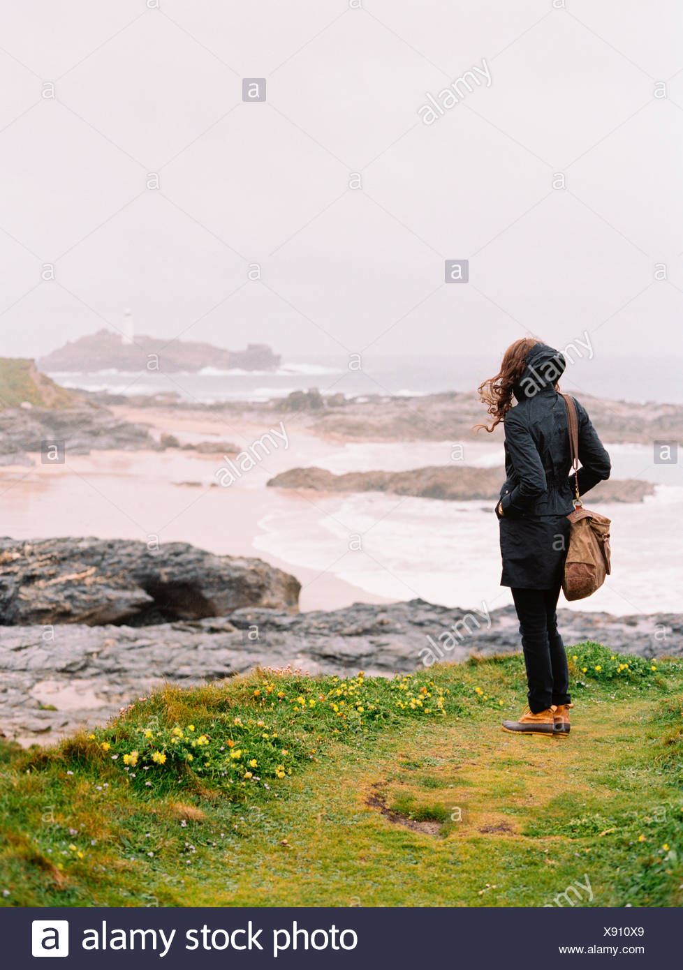 A woman lookng over the rocks and the shoreline on a windy day by the sea. - Stock Image