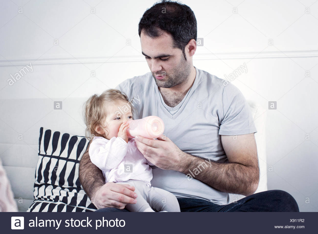 Father holding baby girl on lap, feeding her with bottle - Stock Image