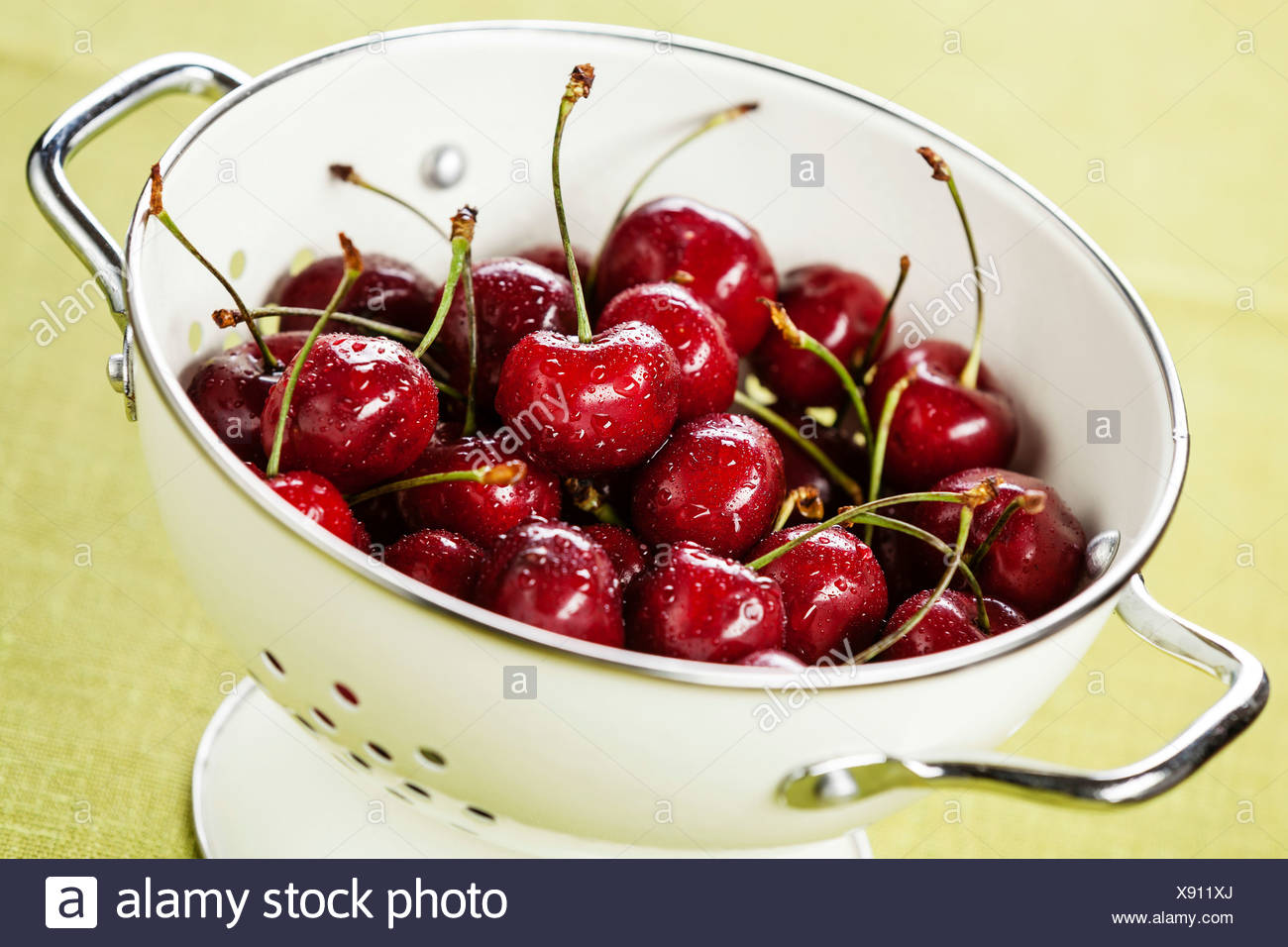 Wet ripe cherries in white colander - Stock Image