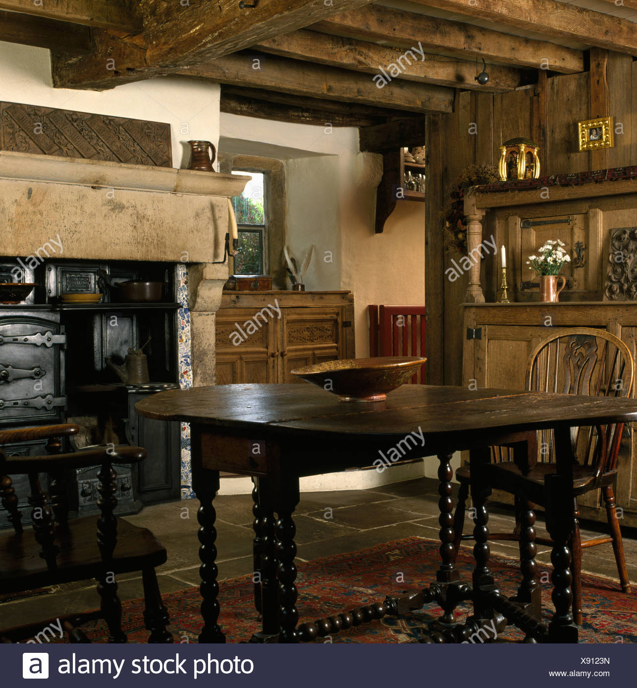 Windsor chairs and Jacobean oak table with barley-twist legs in beamed country dining room with old cast-iron range in fireplace Stock Photo