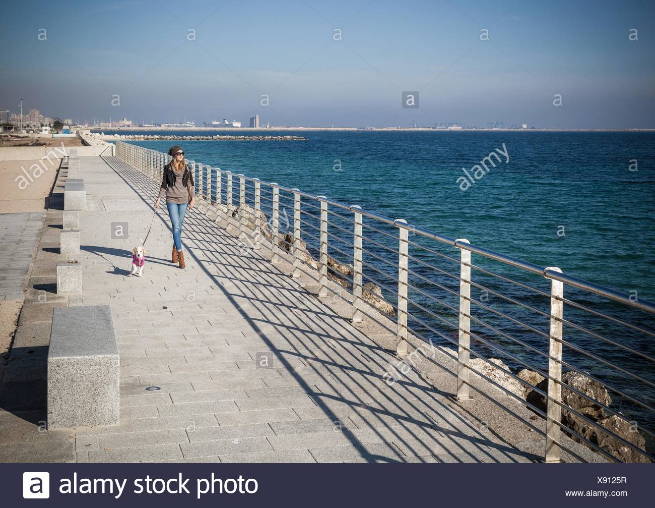 Full length front view young woman walking dog on seafront looking away - Stock Image