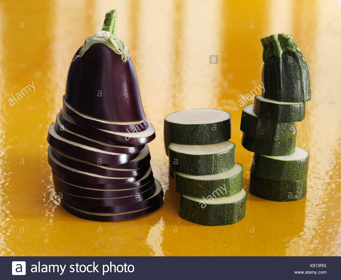 Eggplants and zucchinis cut in round slices - Stock Image