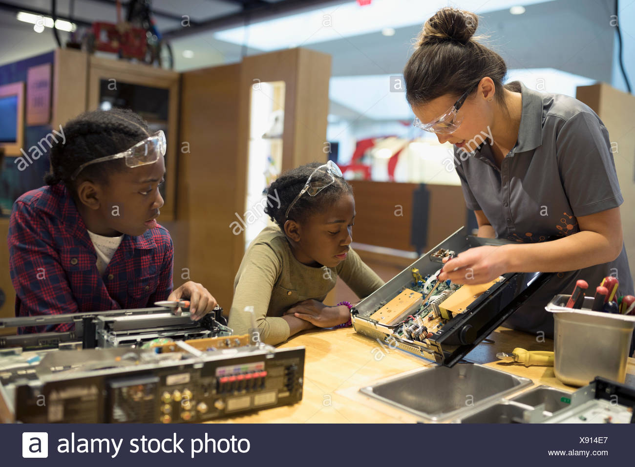 Scientist teaching twin sisters assembling electronics in science center - Stock Image
