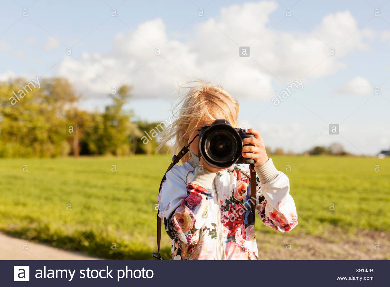 Girl photographing through SLR camera on field against sky - Stock Image