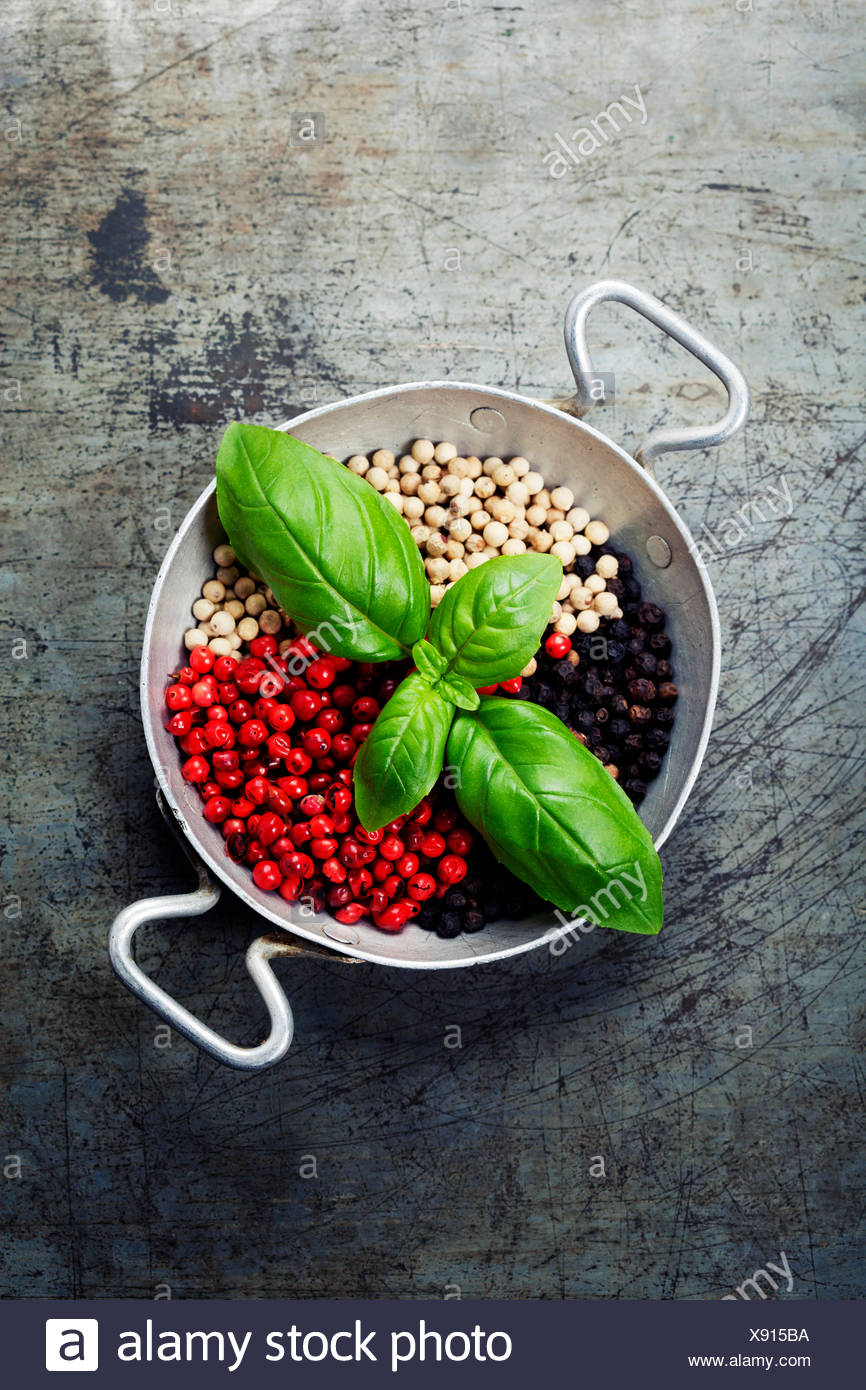 Overhead view of colourful dried pepper mix and basil in bowl on rustic background - Stock Image