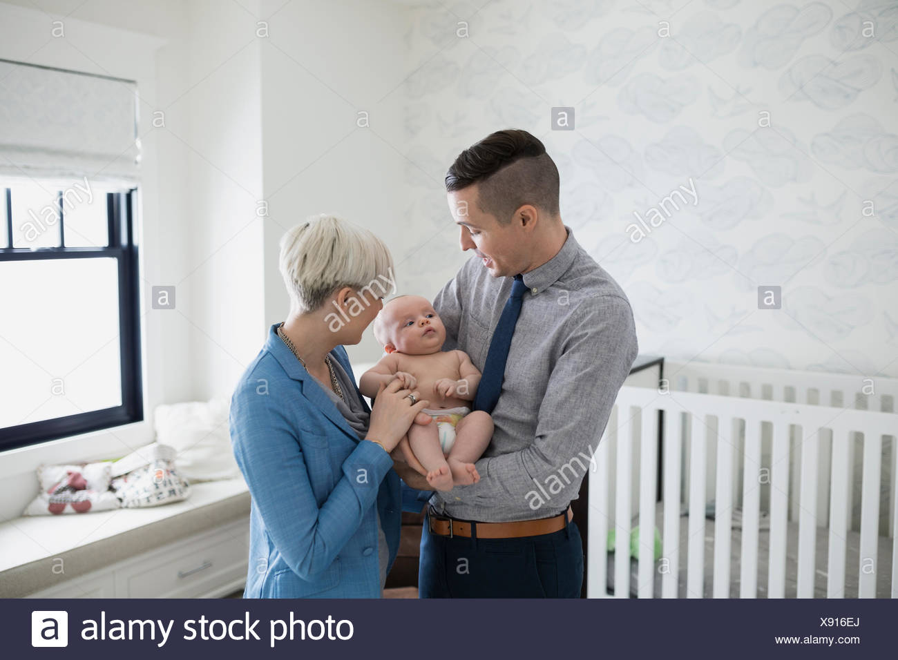 Parents holding baby son in nursery - Stock Image