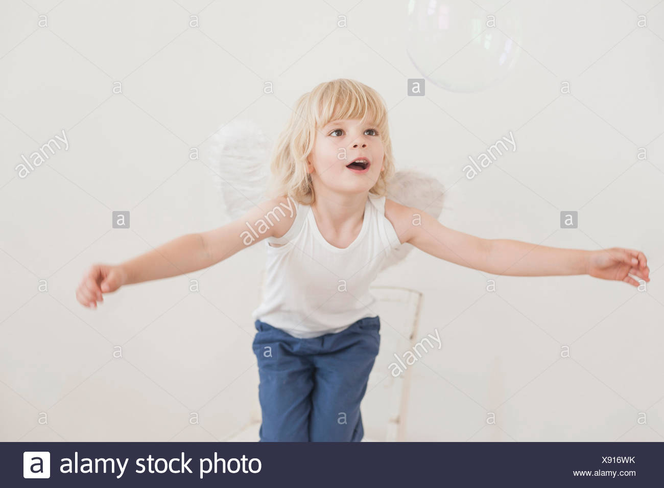 Portrait of gaping little boy with angle wings watching a soap bubble - Stock Image