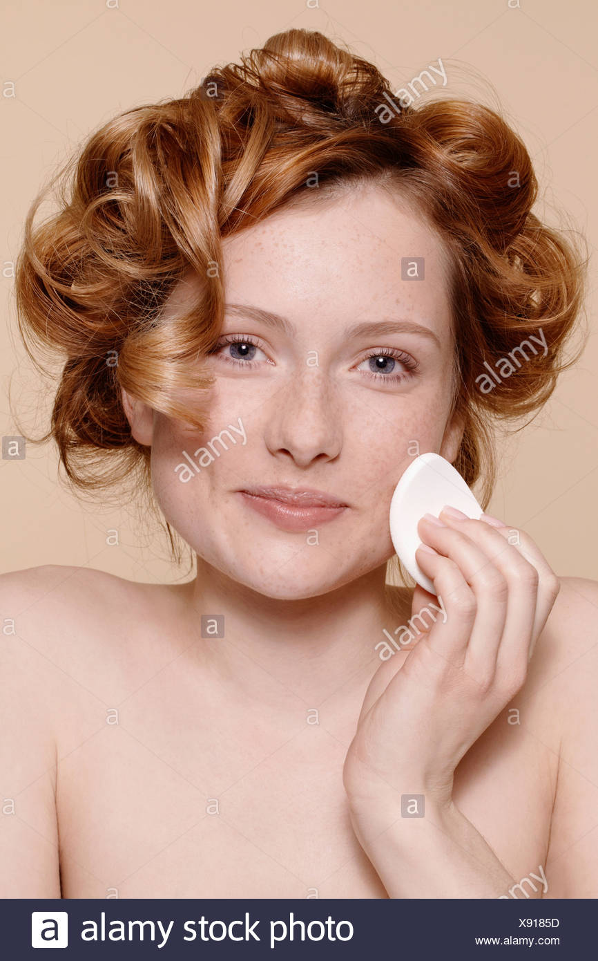 Portrait of young woman cleaning face with cotton wool - Stock Image