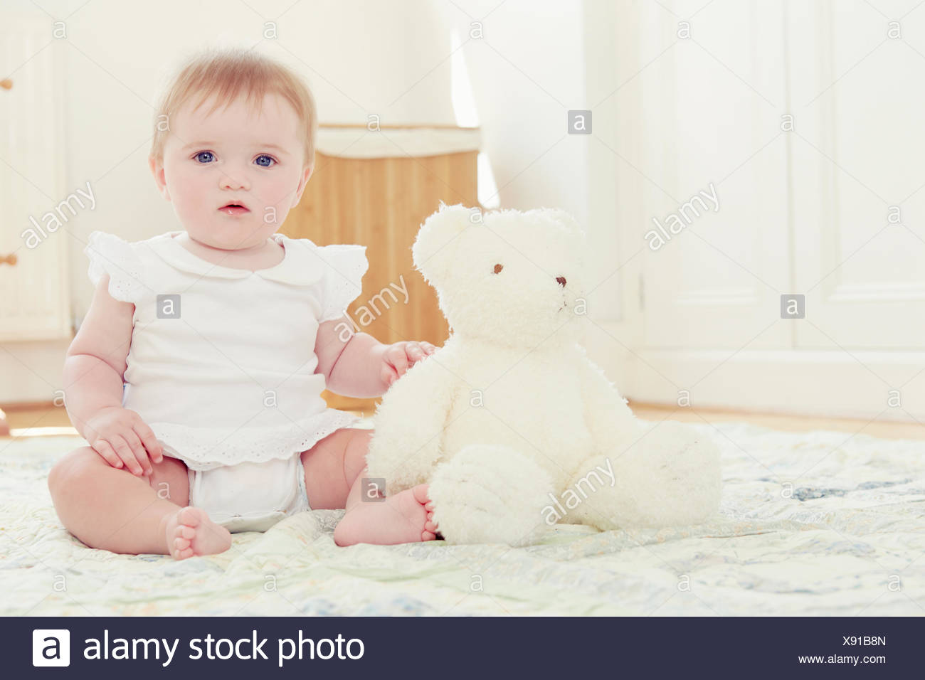 Portrait baby girl and teddy bear sitting on floor - Stock Image