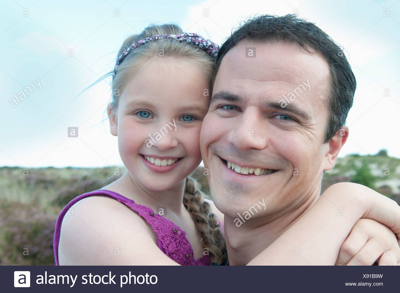 Father and daughter smiling together - Stock Image