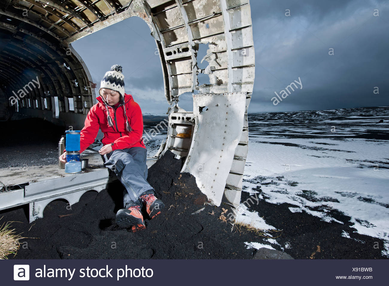 Hiker sitting in airplane wreck in snow - Stock Image