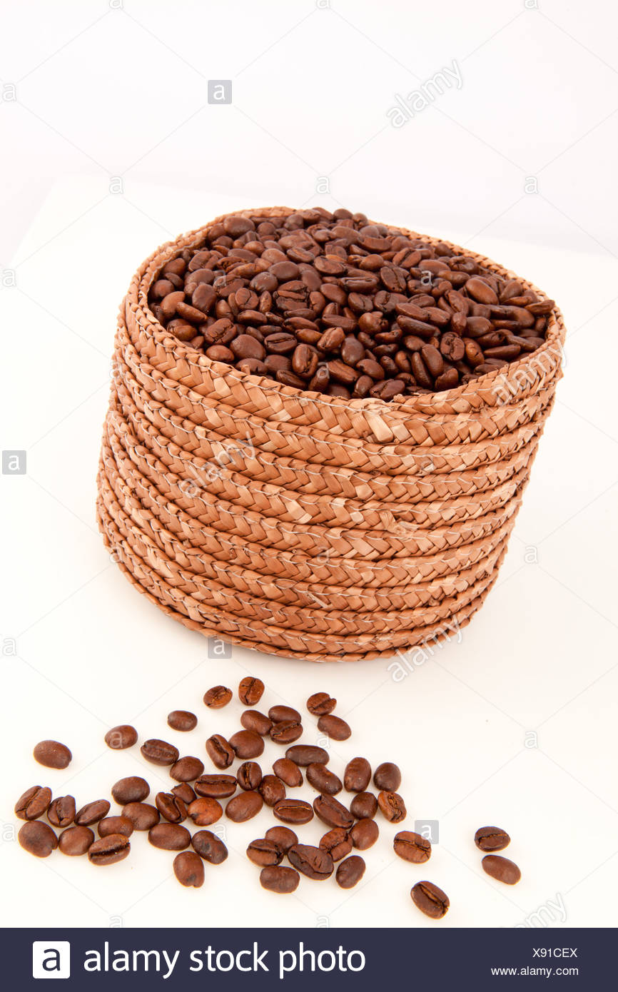 Close up of a basket full of coffee seeds with seeds lying in front of it - Stock Image