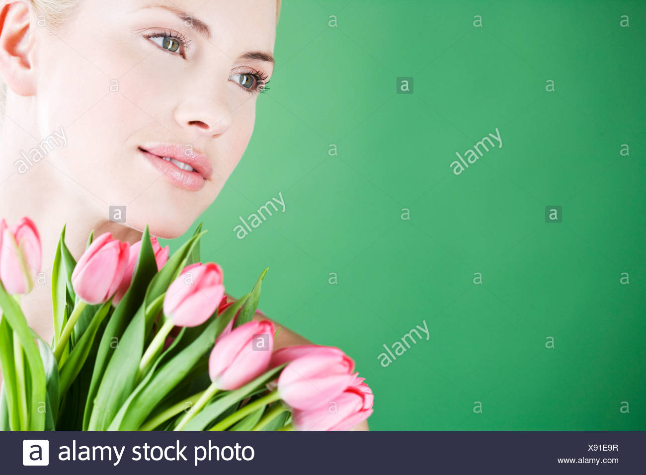 A young woman holding a bunch of pink tulips - Stock Image