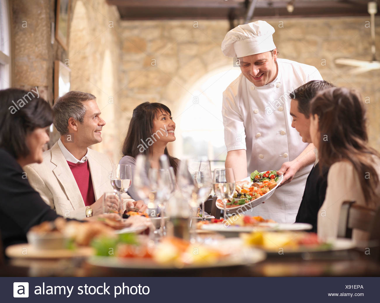 Chef serving people in restaurant - Stock Image