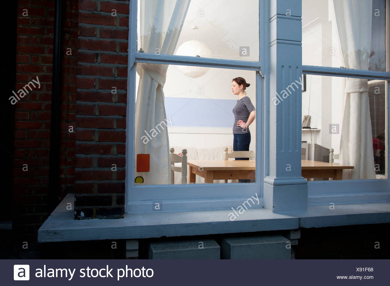 Woman viewed through window - Stock Image