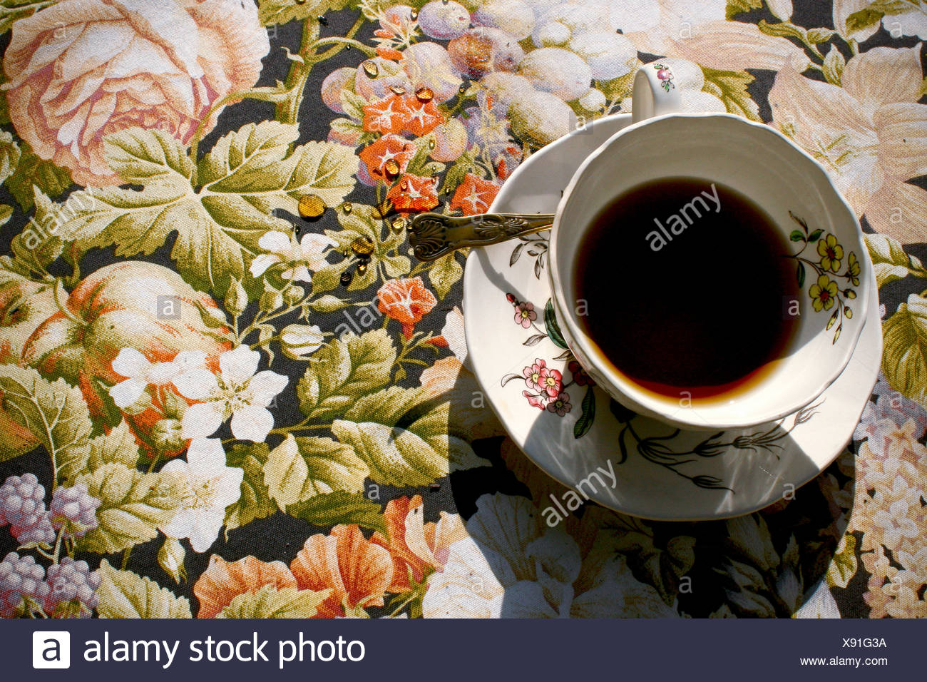 Teacup and saucer on floral tablecloth - Stock Image