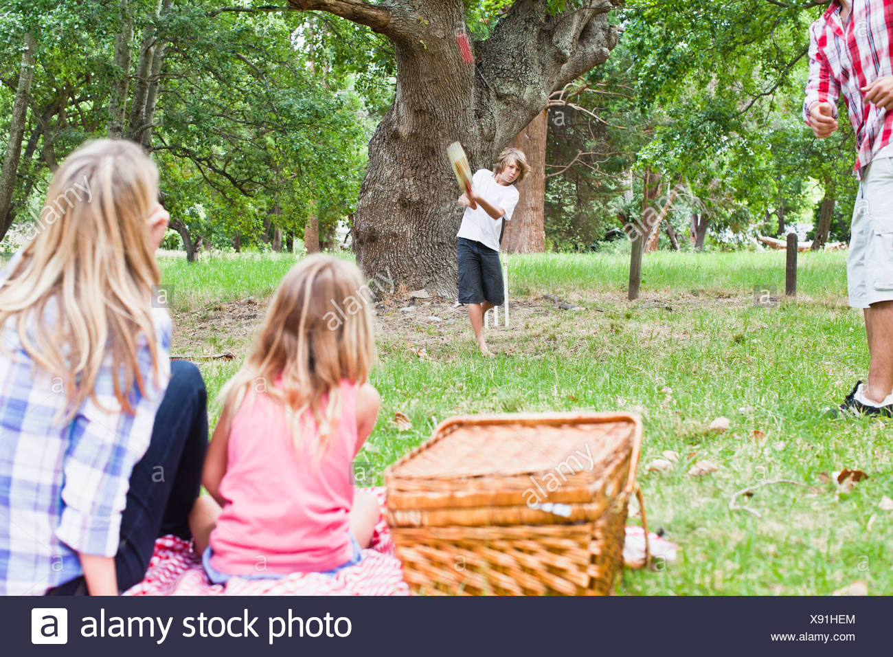 Family relaxing together in park - Stock Image