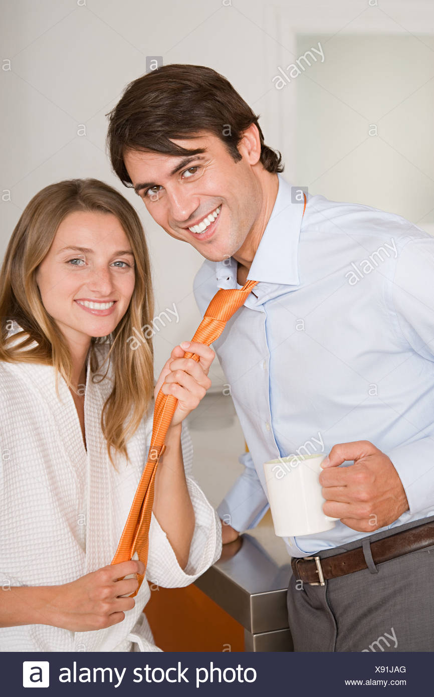 A woman pulling on a mans tie - Stock Image