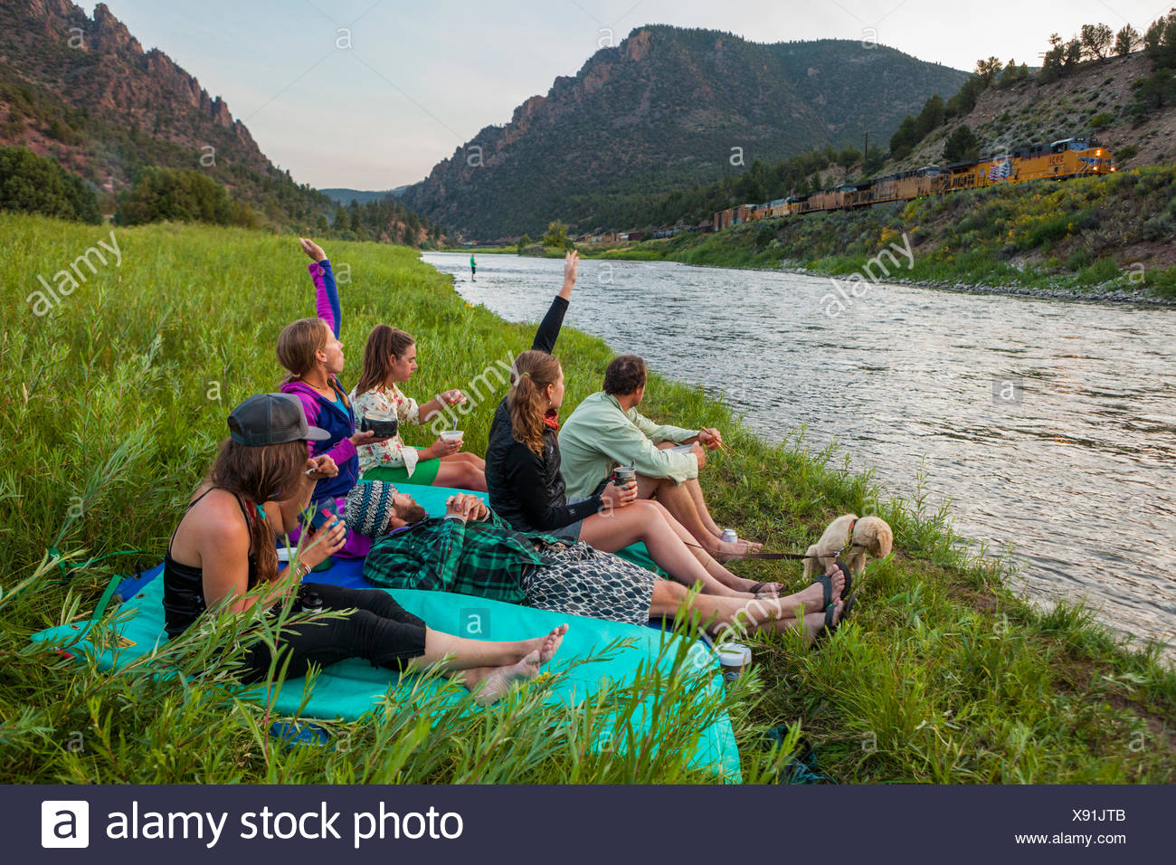 Boaters wave at a passing freight train while eating dinner by the Upper Colorado River at the Benches Campground near Kremmling, Colorado. - Stock Image