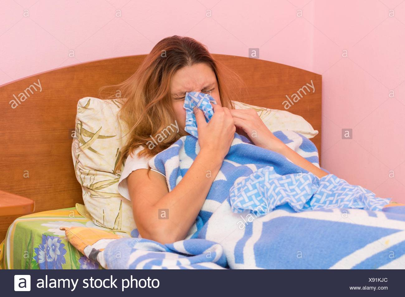 She sneezes ill with acute respiratory illness. - Stock Image