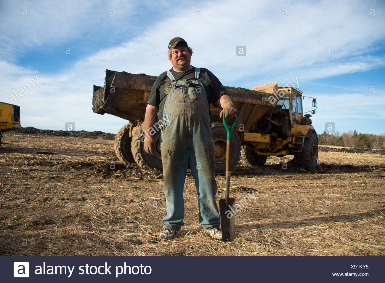 A man stands in front of a truck used for excavation. - Stock Image