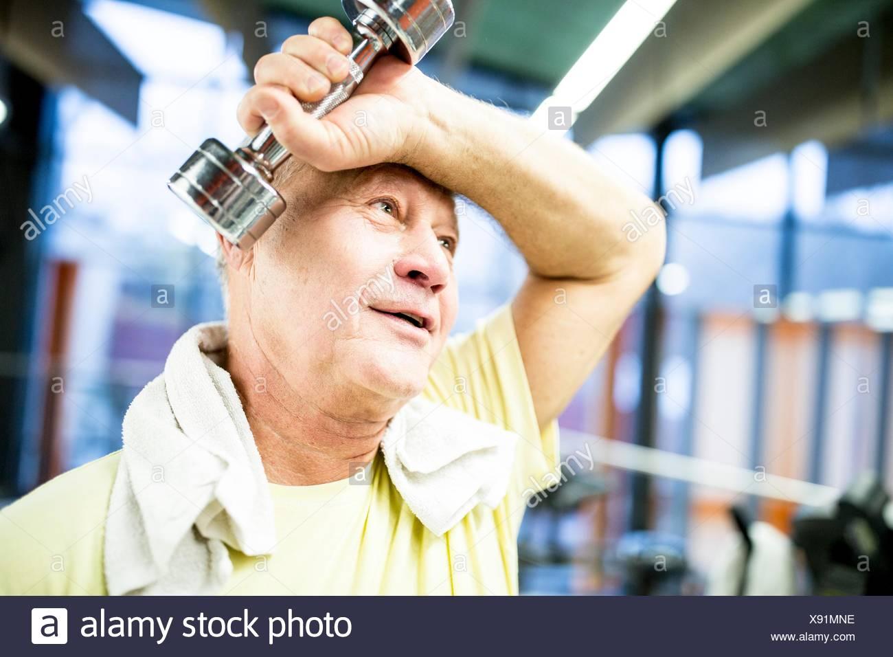 PROPERTY RELEASED. MODEL RELEASED. Senior man holding dumbbell in gym. - Stock Image