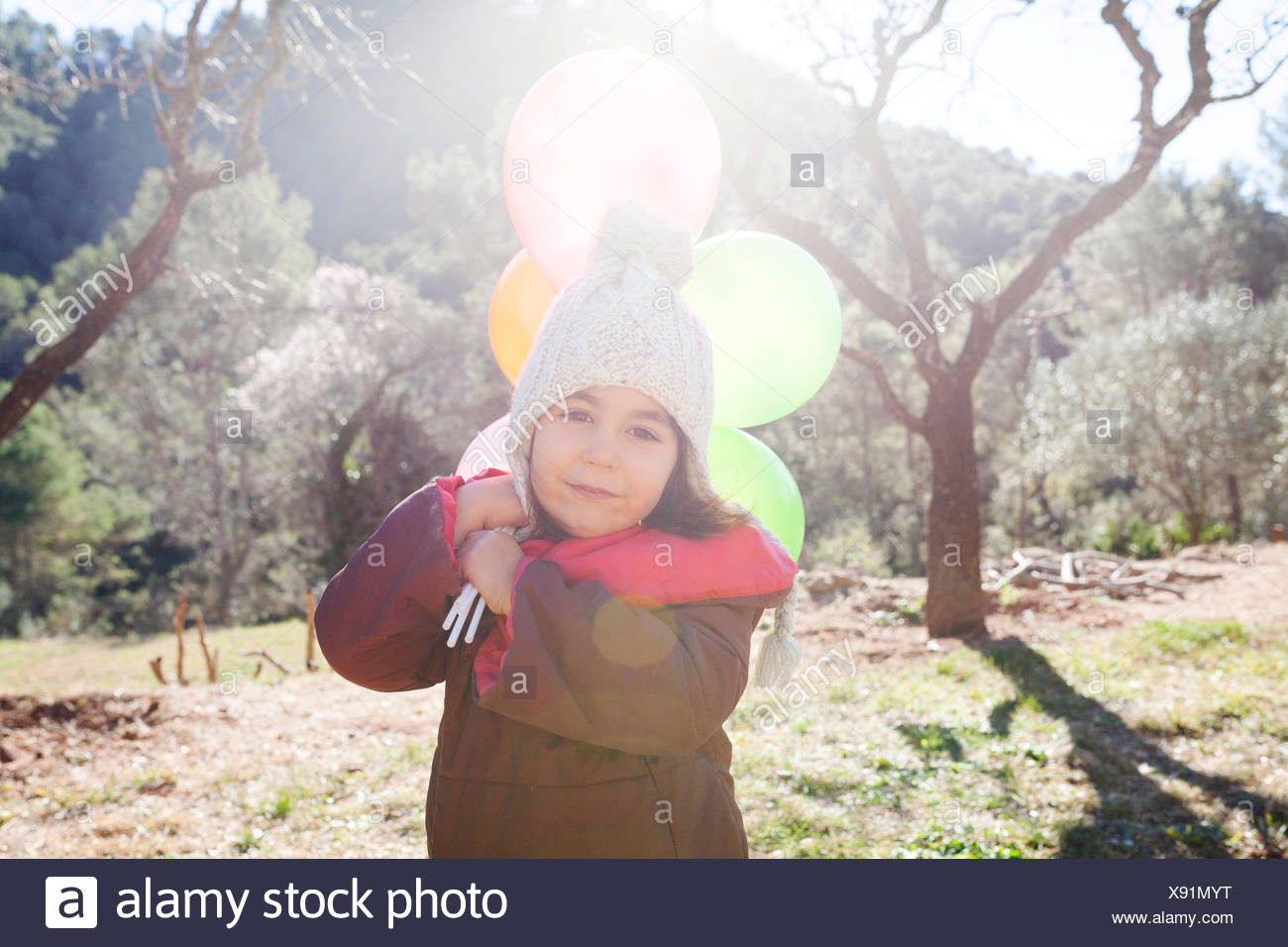 Spain, Gallifa, portrait of little girl with balloons wearing bobble hat - Stock Image