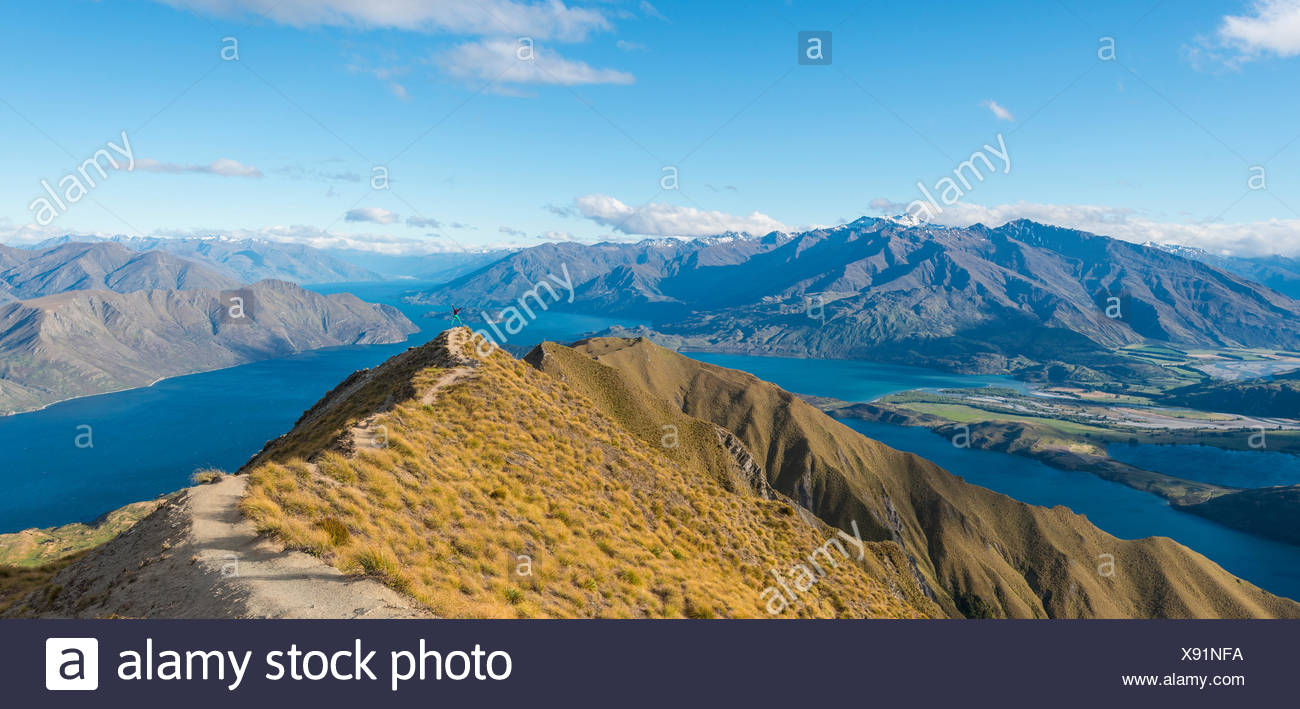 View of mountains and lake, woman jumping at top ridge, Roys Peak, Lake Wanaka, Southern Alps, Otago Region, Southland - Stock Image