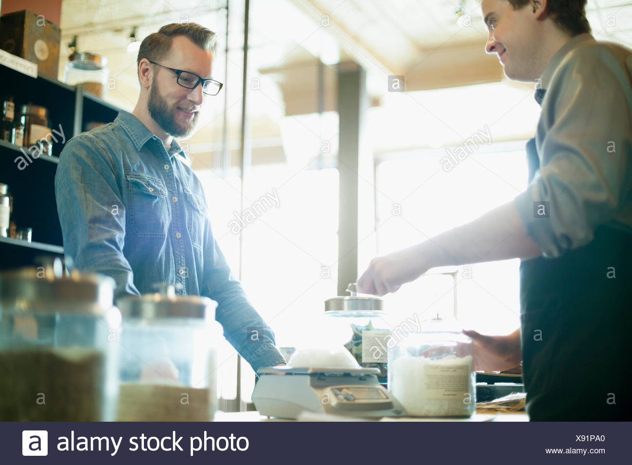 merchant offering product in spice store - Stock Image