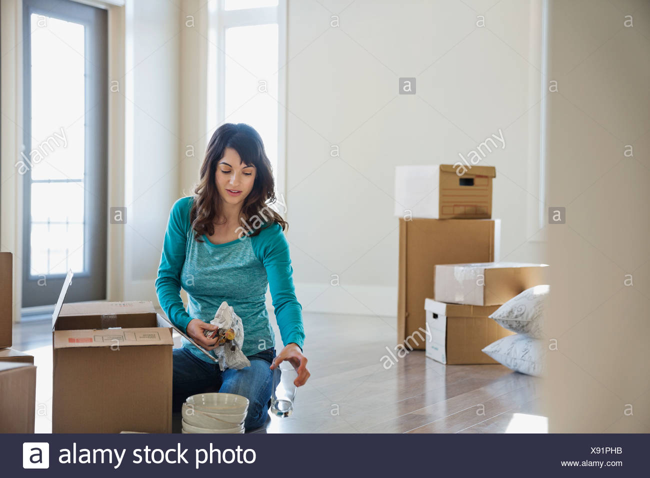 Woman unpacking cardboard boxes in new home - Stock Image
