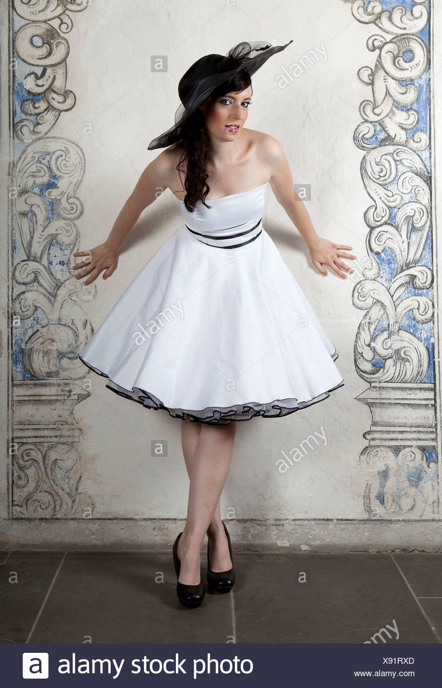 Young woman wearing a hat and a white dress - Stock Image