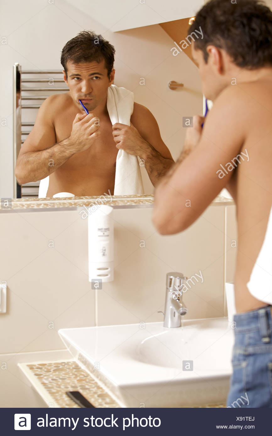 Reflection in a bathroom mirror of a young man brushing his teeth - Stock Image