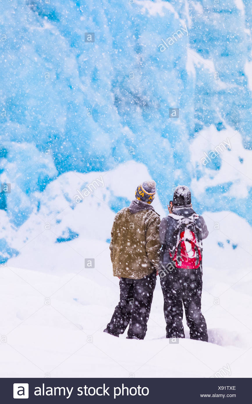 A couple snowshoes across Portage Lake during a heavy snowfall in winter to see the terminus of Portage Glacier, Southcentral Alaska, USA - Stock Image