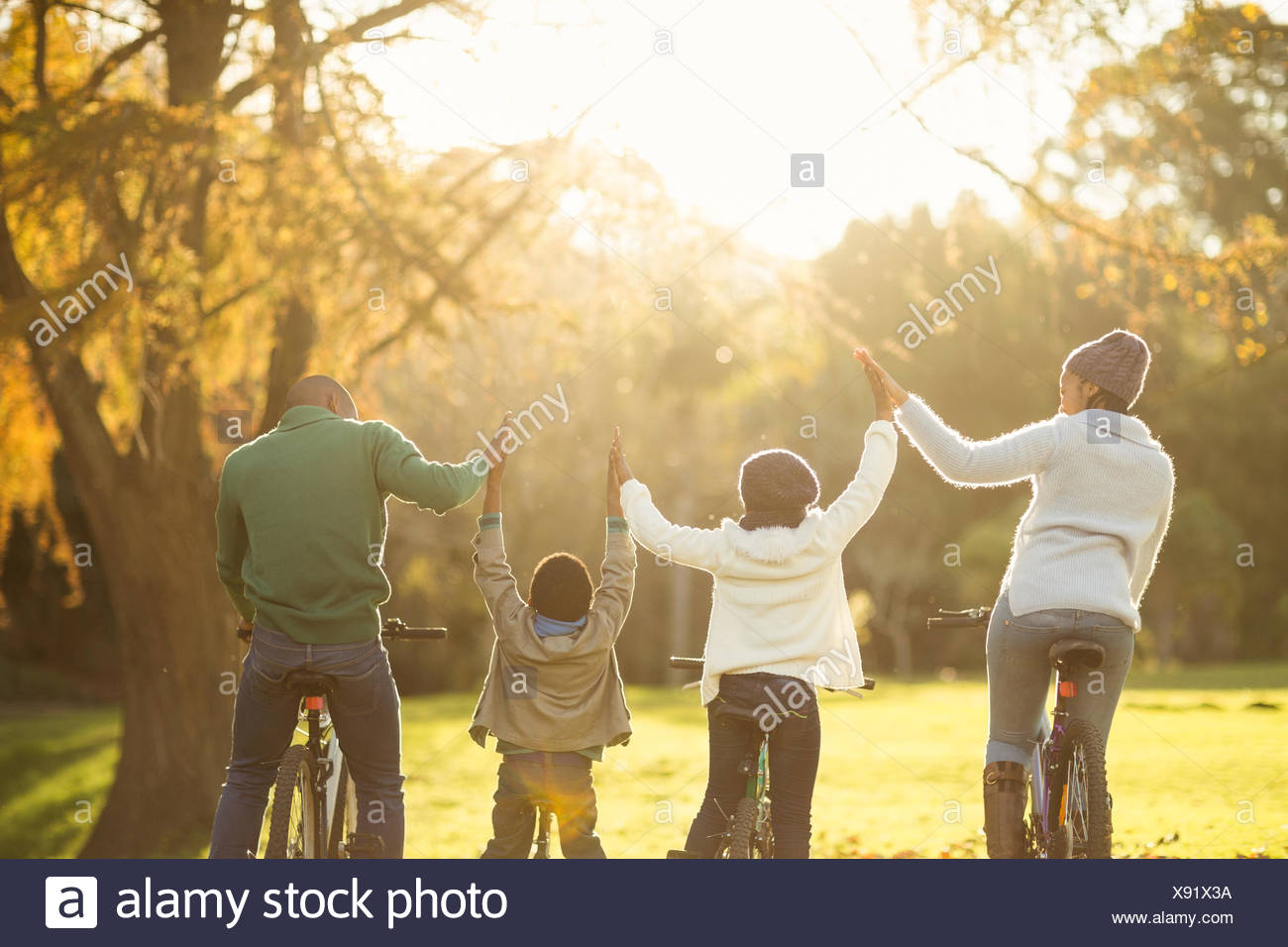 Rear view of a young family with arms raised on bike - Stock Image
