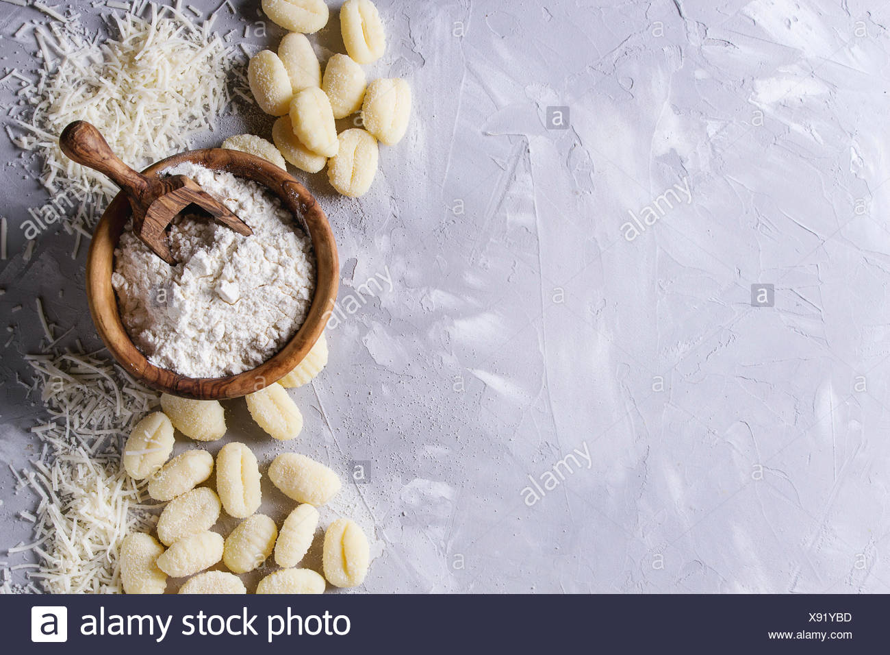 Raw uncooked potato gnocchi with olive wood bowl of flour, grated parmesan cheese over gray concrete background. Top view with copy space. Home cookin - Stock Image
