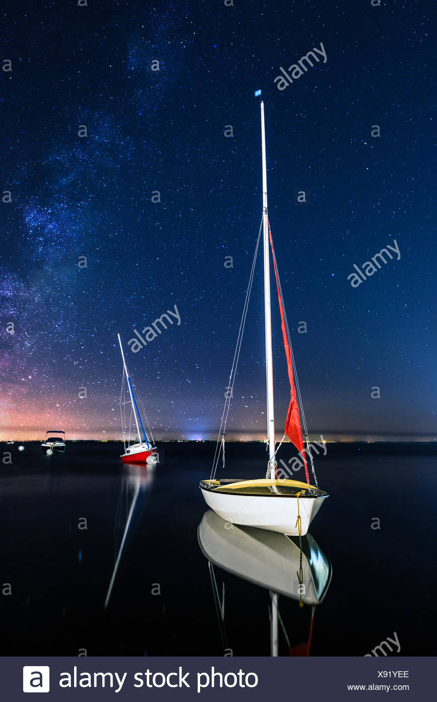 Three sailing boats anchored at night - Stock Image