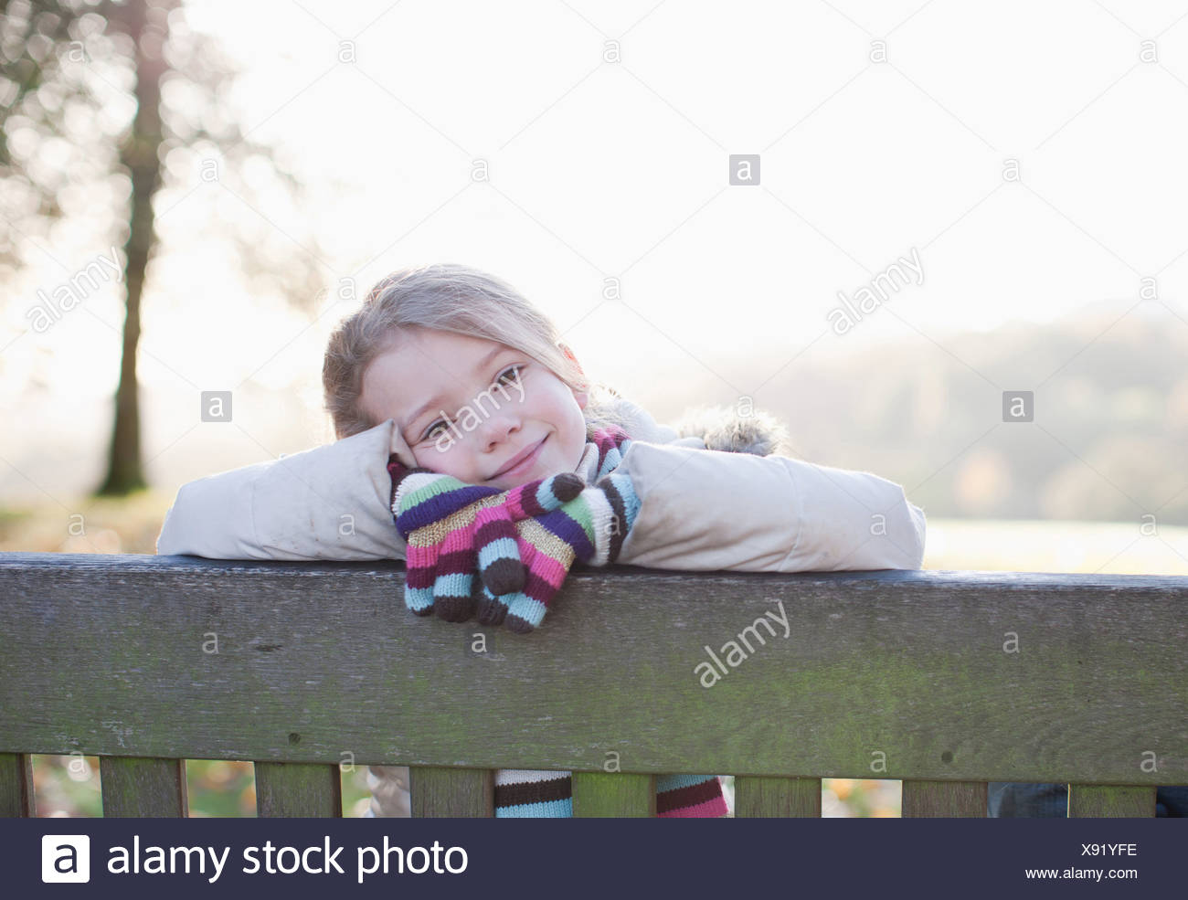 Girl sitting on bench outdoors in autumn - Stock Image