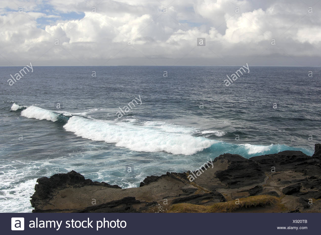 White surf waves of the vast Indian Ocean rolling on the Southern beach of the island of Mauritius - Stock Image