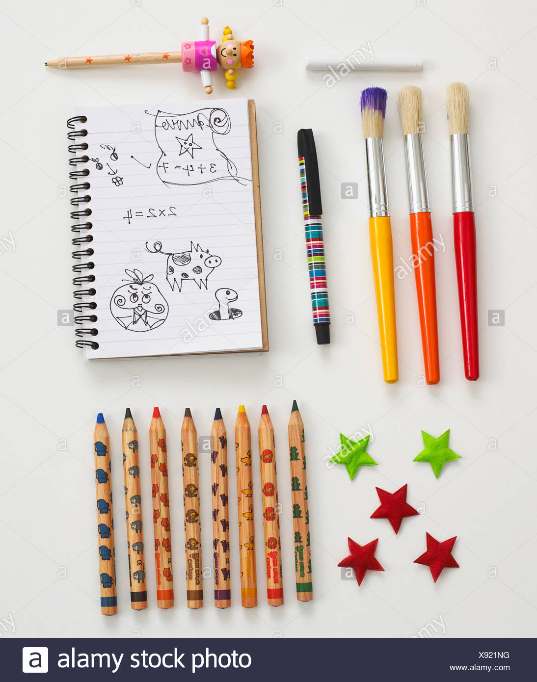 Assorted stationary including paintbrushes, pencils and notepad - Stock Image